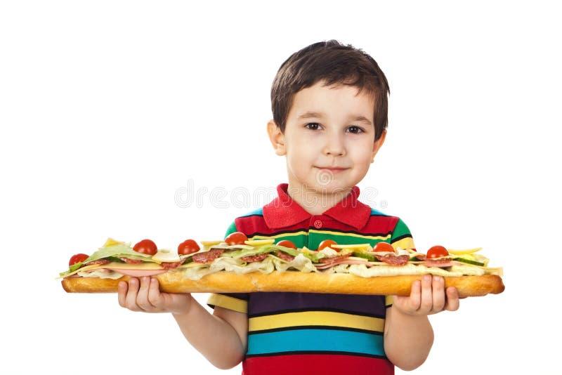 De jongen houdt een lange sandwich stock foto