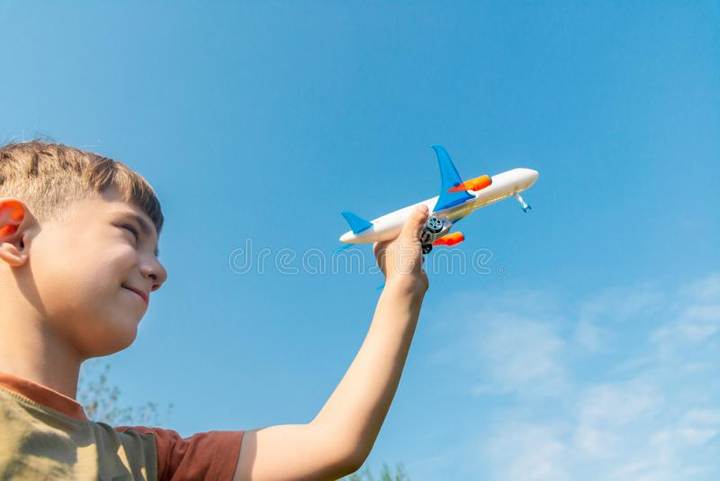 De jongen houdt een vliegtuig in zijn hand tegen de blauwe hemel royalty-vrije stock afbeelding