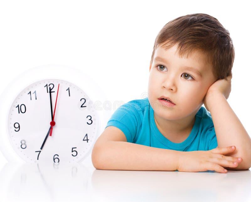 De jongen houdt grote klok stock afbeeldingen