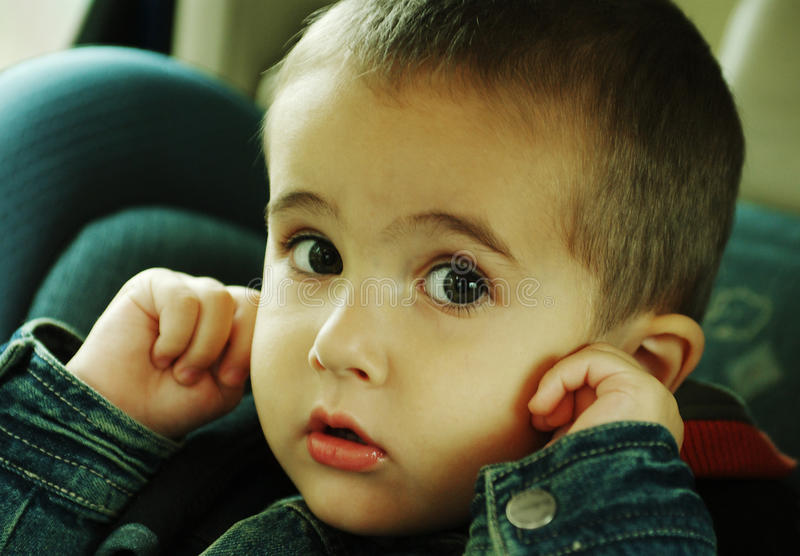 De jongen houdt omhoog zijn oren tegen royalty-vrije stock afbeeldingen