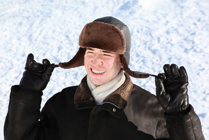 De jongen houdt op touwwerk oor-kleppen hoed stock afbeelding