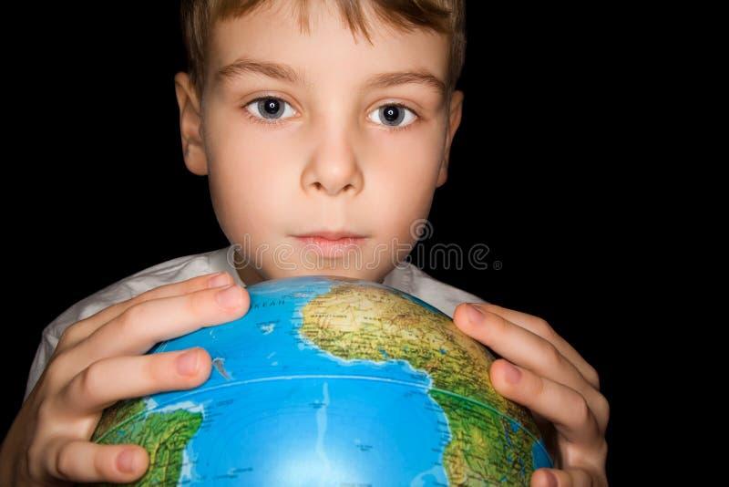De jongen houdt overhandigt binnen bol van geïsoleerder wereld stock afbeelding