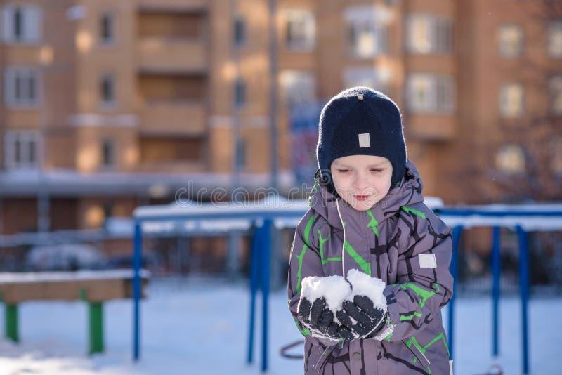 De jongen houdt sneeuw in handen Gelukkig jong geitje die in openlucht in de winterstad lopen Kind die en pret glimlachen hebben stock afbeelding