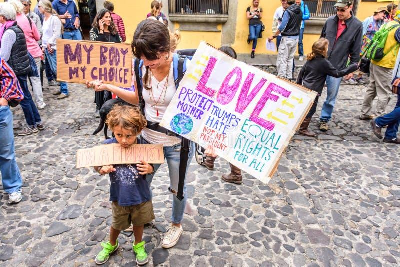 De jongen houdt teken in Vrouwen ` s Maart, Antigua, Guatemala stock fotografie