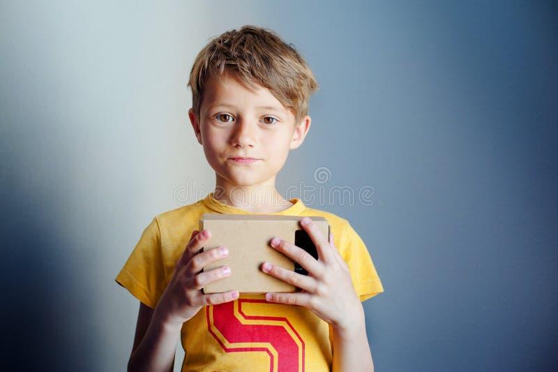 De jongen houdt virtuele werkelijkheid googles, VR, blauwe achtergrond stock afbeeldingen