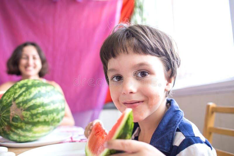 De jongen houdt in zijn handen een stuk van watermeloen en glimlacht stock afbeeldingen