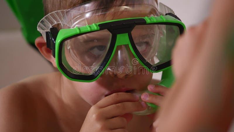 De jongen imiteert het zwemmen op de laag, en het meisje blaast bellen op hem, omhoog sluit royalty-vrije stock afbeeldingen