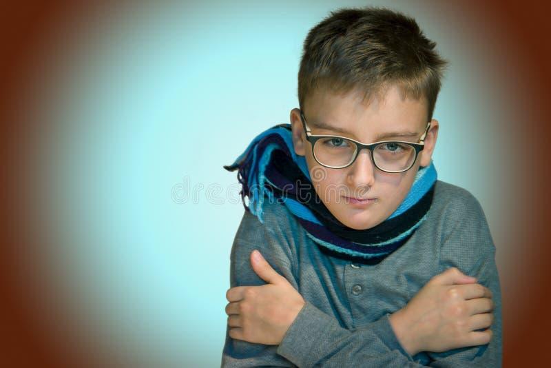 De jongen 10 jaar hij ziek was zit koude, royalty-vrije stock fotografie