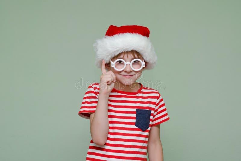 De jongen in Kerstman` s hoed en glazen houdt zijn wijsvinger tegen P royalty-vrije stock foto's