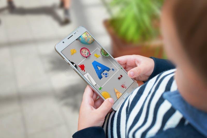 De jongen keurt brieven op mobiele app goed en leert door het spel royalty-vrije stock afbeelding