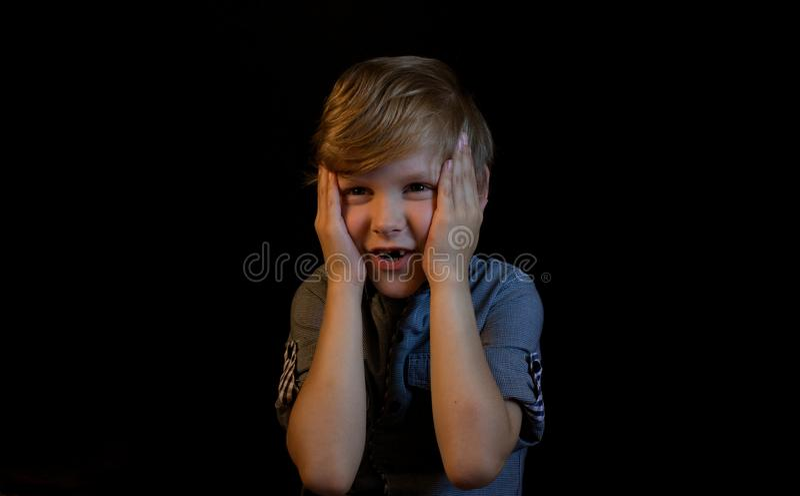De jongen kijkt met verbazing Handen die zijn hoofd houden stock foto