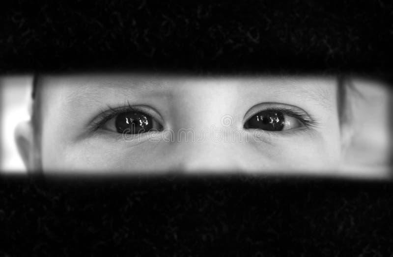 De jongen kijkt met vrees door de barst royalty-vrije stock afbeeldingen