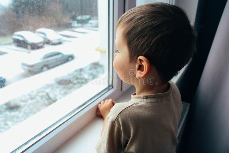 De jongen kijkt uit het venster stock afbeelding
