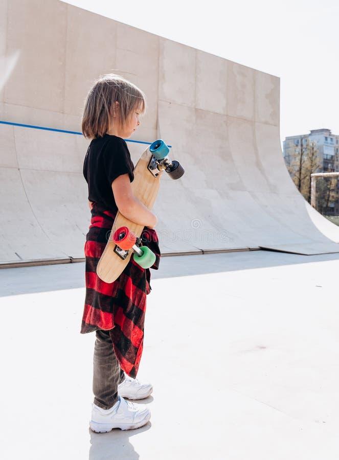 De jongen kleedde zich in de vrijetijdskleding met skateboard in zijn handtribunes in een vleetpark naast de dia bij zonnig stock foto's