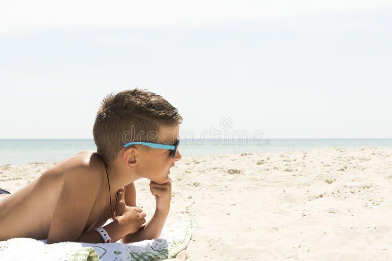De jongen lacht en werpt zand op zijn hoofd liggend op het zand tegen de blauwe hemel stock afbeeldingen