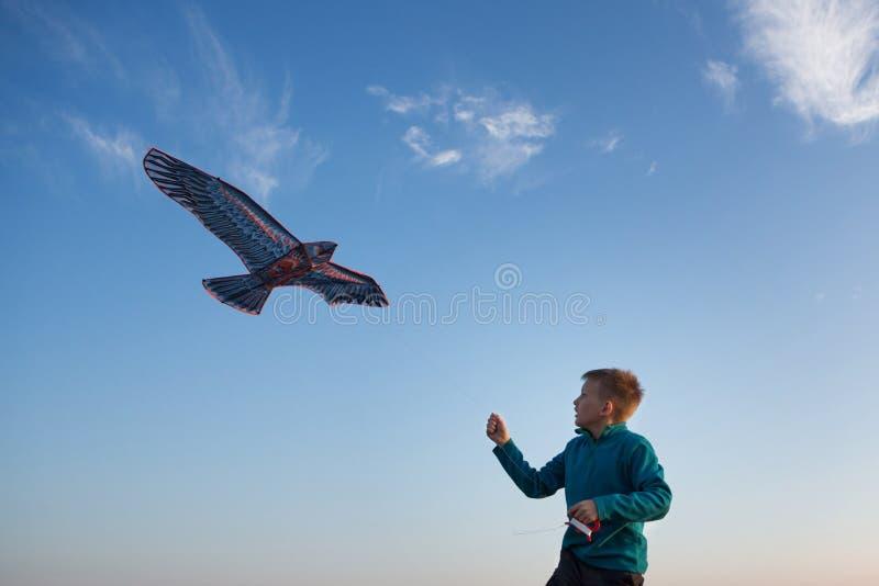 De jongen lanceert een vlieger Het vliegen van de vlieger Mooie Zonsondergang Bergen, overzees, landschap Zonnige de zomerdag ade royalty-vrije stock foto