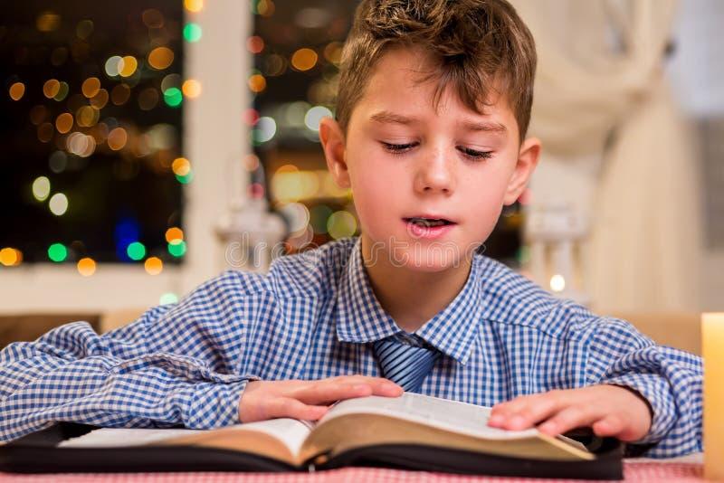 De jongen leest een dik boek stock foto