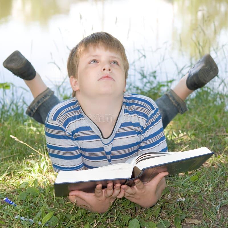 De jongen leest een groot boek stock fotografie