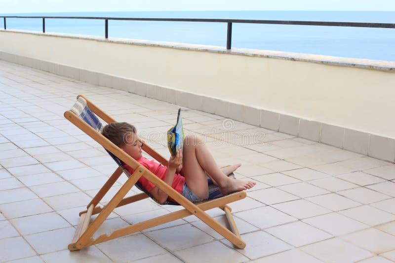De jongen leest in zitkamer op veranda stock afbeelding