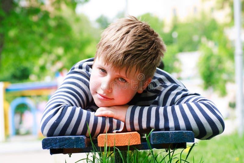 De jongen legt op een bank in het park stock afbeelding