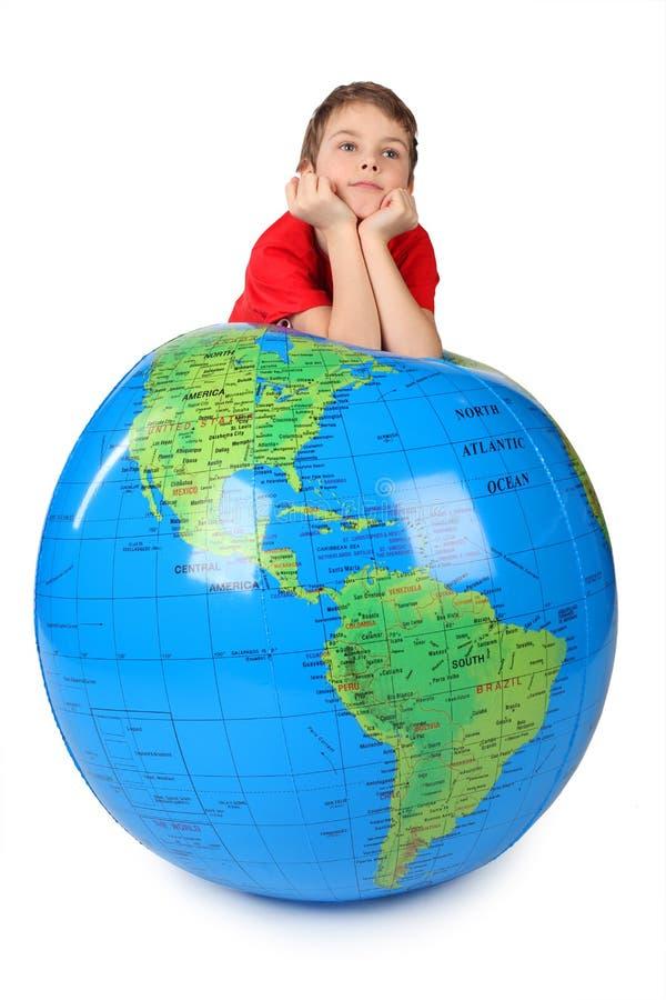 De jongen leunt op opblaasbare bolkin op handen stock afbeelding