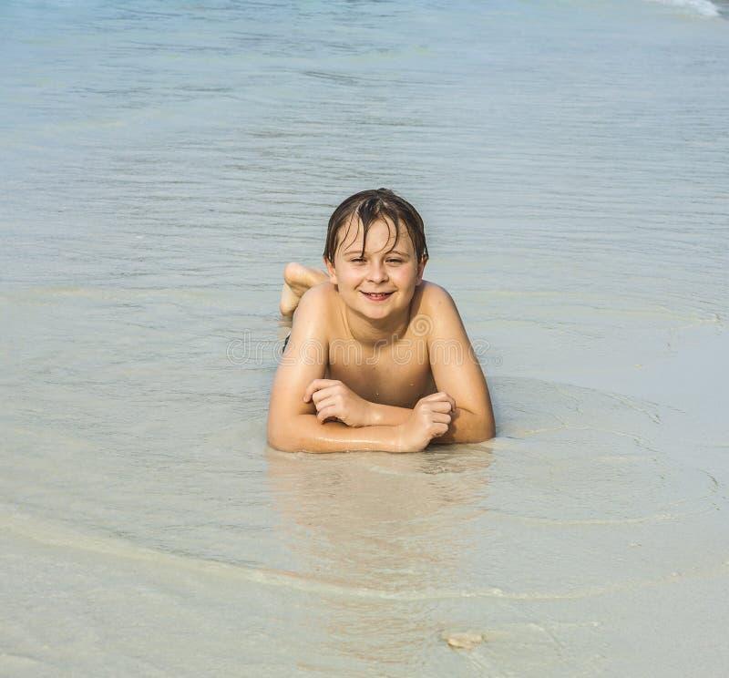 De Gelukkige Jongen Met Nat Haar Bij Het Strand Glimlacht En Kijkt Zeer Zelf Stock Afbeelding