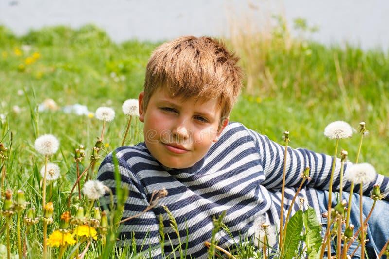 De jongen ligt op gras dichtbij de rivier royalty-vrije stock foto's