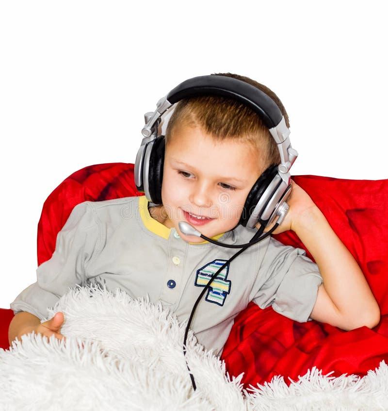 De jongen ligt op het bed en luistert aan muziek met hoofdtelefoons royalty-vrije stock afbeeldingen