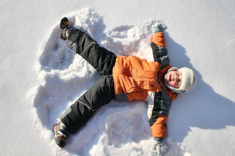 De jongen ligt op sneeuw