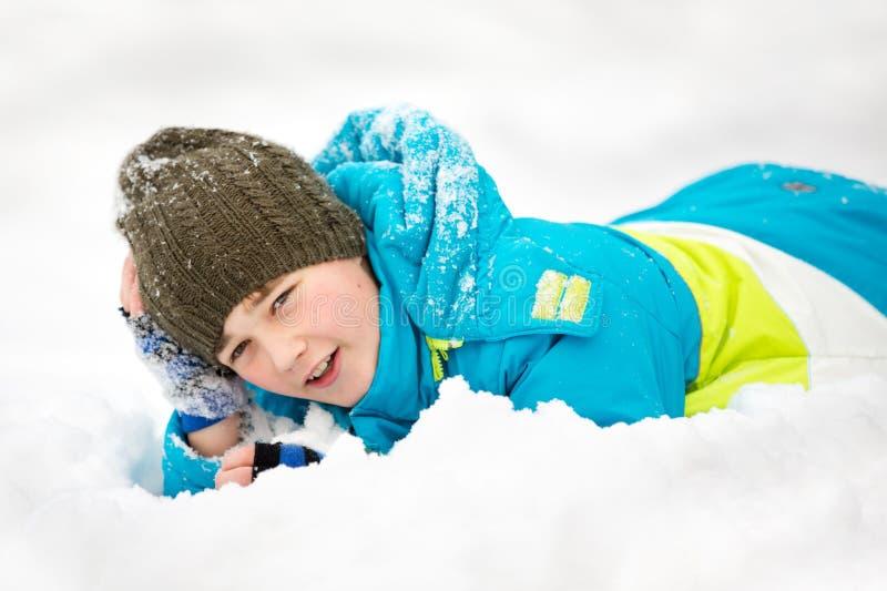De jongen ligt op sneeuw stock afbeeldingen