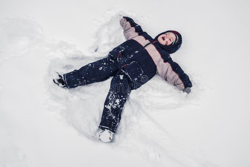De jongen ligt op de sneeuw van de het noordenpool stock afbeelding