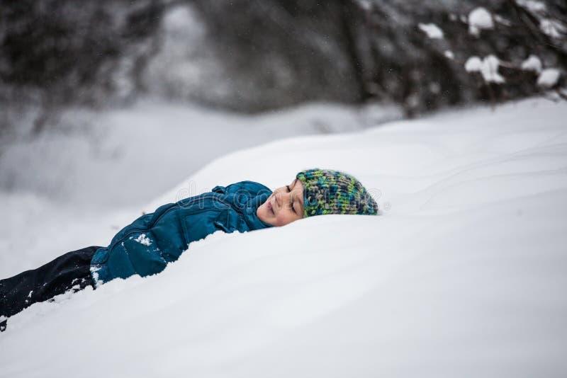 De jongen ligt in de sneeuw stock foto