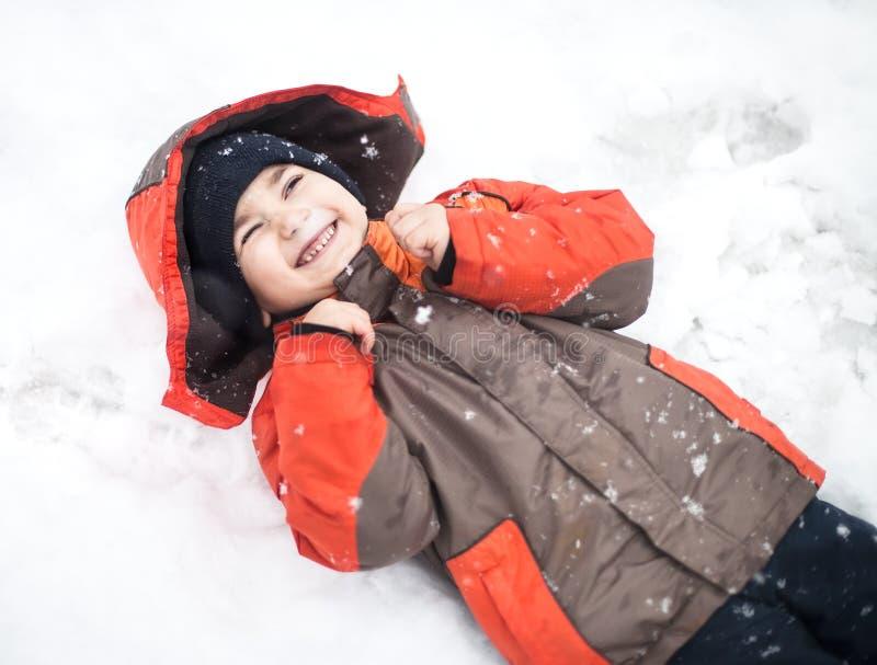 De jongen ligt in sneeuw royalty-vrije stock fotografie