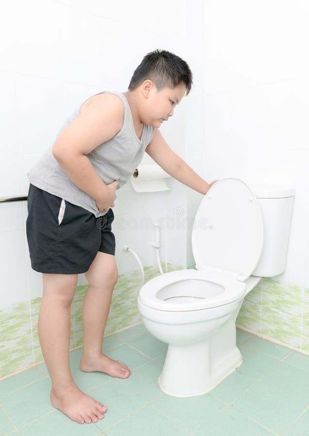 De jongen lijdt aan maag en braakt in toilet, diarree royalty-vrije stock afbeeldingen