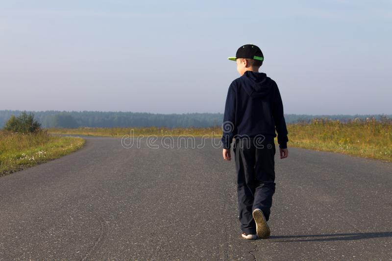 De jongen loopt in het midden van de weg royalty-vrije stock afbeeldingen