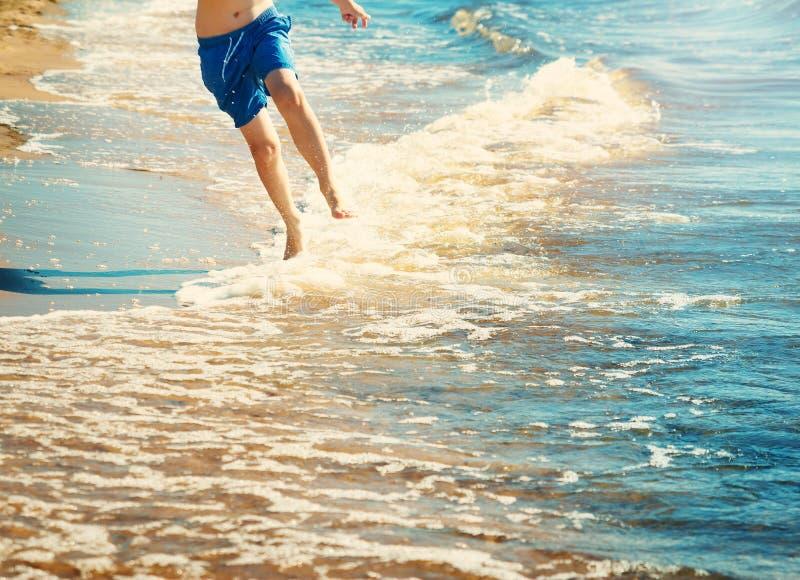 De jongen loopt op het strand stock foto
