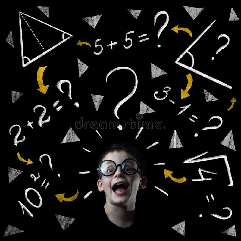 De jongen lost wiskundevoorbeelden bij het bord op royalty-vrije stock afbeeldingen