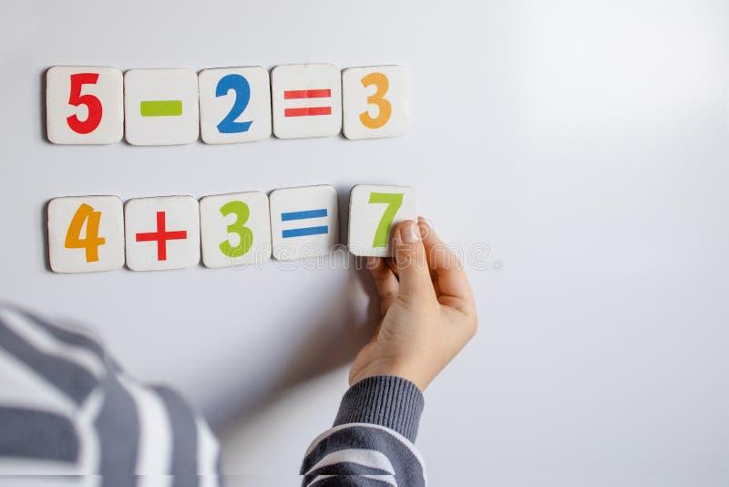 De jongen lost wiskundige voorbeelden op Een kind lost voorbeelden op een bord op stock foto