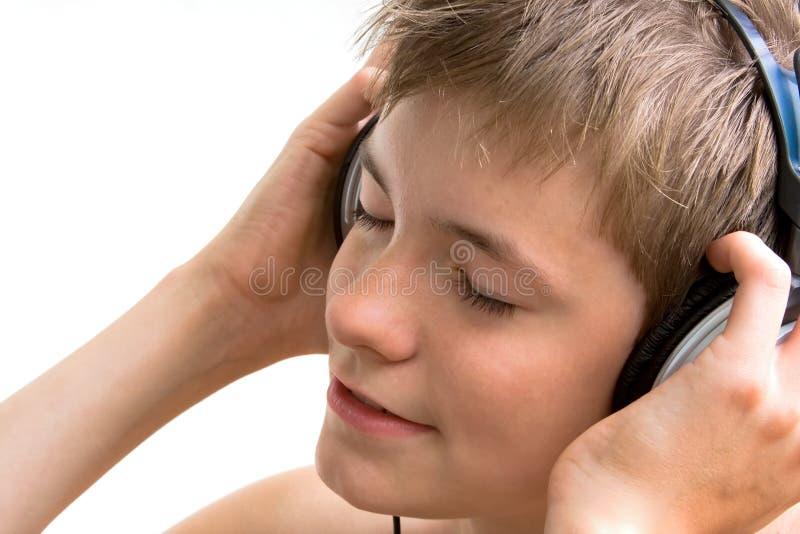 De jongen luistert aan muziek royalty-vrije stock fotografie