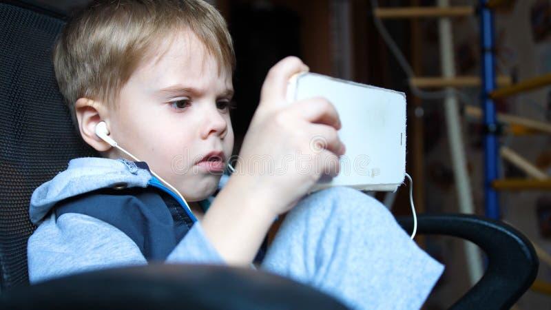 De jongen luistert aan muziek door hoofdtelefoons In de ruimte van de kinderen geniet het kind van muziek stock foto's