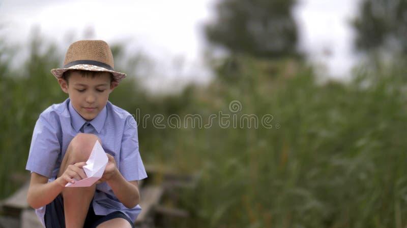 De jongen maakt een document boot op aard, voorbereidingen treft om het in de rivier te lanceren stock afbeeldingen