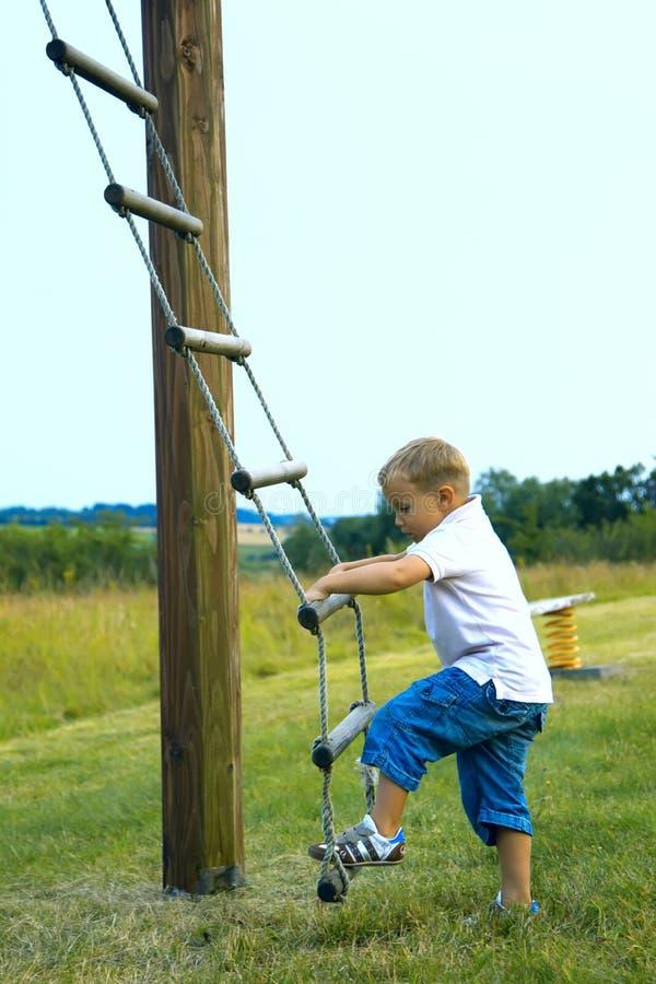 De jongen maakt een klim stock afbeeldingen