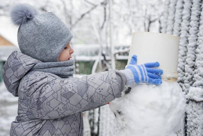 De jongen maakt een sneeuwman Aanbiddelijke jong geitjejongen die een sneeuwman maken, en pret met sneeuw, in openlucht op koude  royalty-vrije stock fotografie