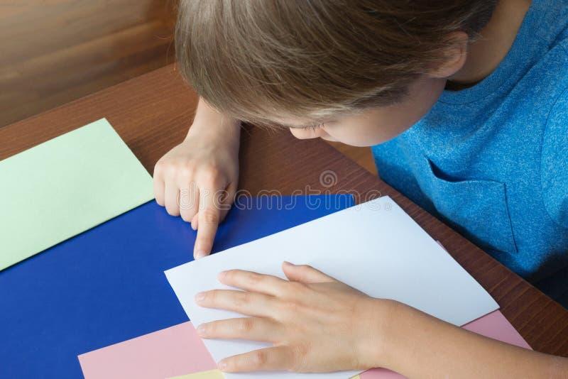 De jongen maakt groetkaart gebruikend gekleurd document stock fotografie