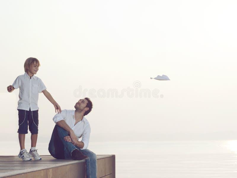 De jongen maakt vlieg zijn document vliegtuig met zijn vader ` s help stock afbeeldingen