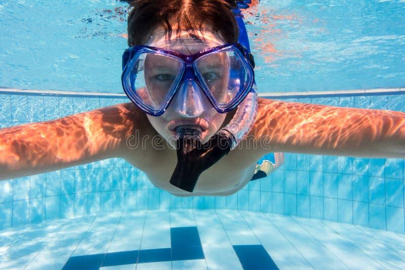 De jongen in masker duikt in zwembad stock foto
