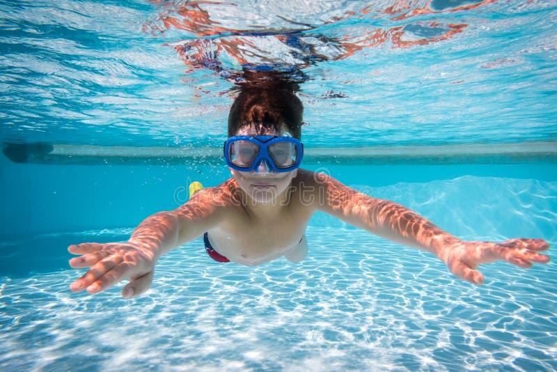 De jongen in masker duikt in zwembad stock fotografie