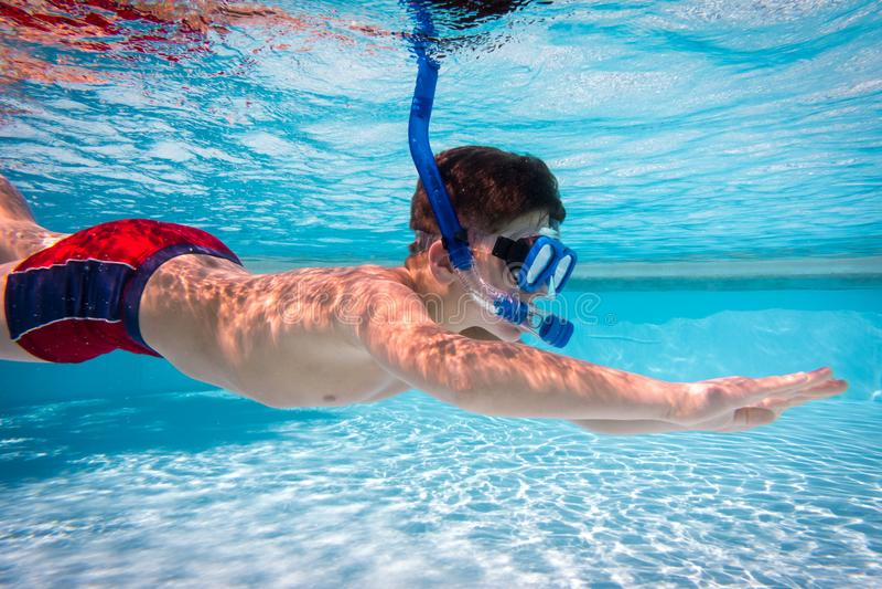 De jongen in masker duikt in zwembad royalty-vrije stock afbeeldingen