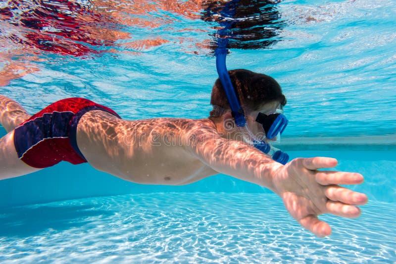 De jongen in masker duikt in zwembad stock afbeeldingen