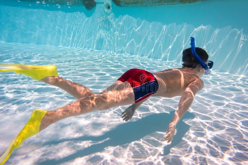 De jongen in masker duikt in zwembad royalty-vrije stock afbeelding